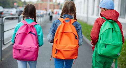 3 children with rucksacks going to school